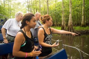 People on Airboat pointing and looking at wildlife in water